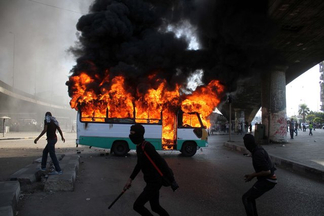 """Egyptian protesters clash near a bus belonging to Muslim Brotherhood supporters burns after it was reportedly set alight by anti- government protesters in Cairo, Egypt, Friday, April 19, 2013. Clashes erupted Friday between several hundred opponents and supporters of Egypt's Islamist president during a rally by his allies calling on him to """"cleanse the judiciary"""" of alleged supporters of the old regime. (Photo by Mostafa Elshemy/AP Photo)"""