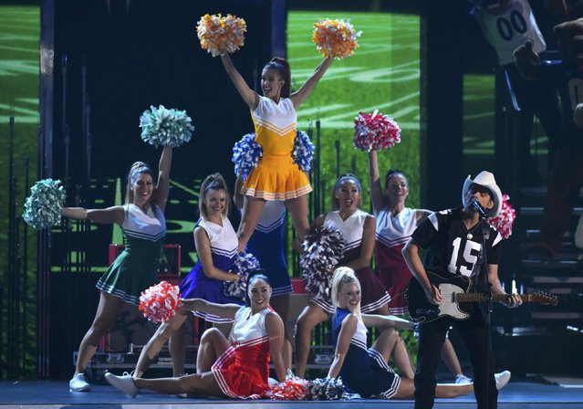 "Brad Paisley is accompanied by cheerleaders as he performs ""Country Nation"" at the 49th Annual Country Music Association Awards in Nashville, Tennessee November 4, 2015. (Photo by Harrison McClary/Reuters)"