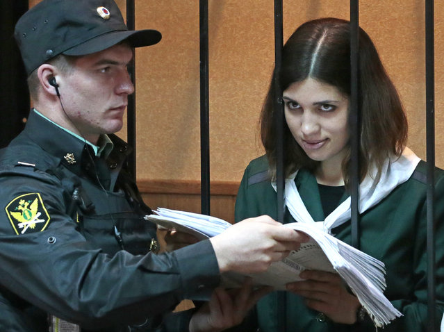 Nadezhda Tolokonnikova, a member of the feminist punk band, p*ssy Riot, right, reads papers at a district court in Zubova Polyana 440 km southeast of Moscow in Russia's province of Mordovia, Friday, April 26, 2013. A Russian court is to consider whether one of the jailed p*ssy Riot members is eligible for early release. Nadezhda Tolokonnikova, in custody since her arrest in March 2012, is serving a two-year sentence for the band's irreverent protest against President Vladimir Putin in Moscow's main cathedral. Tolokonnikova's lawyer Irina Khrunova is at right.(AP Photo/Mikhail Metzel)