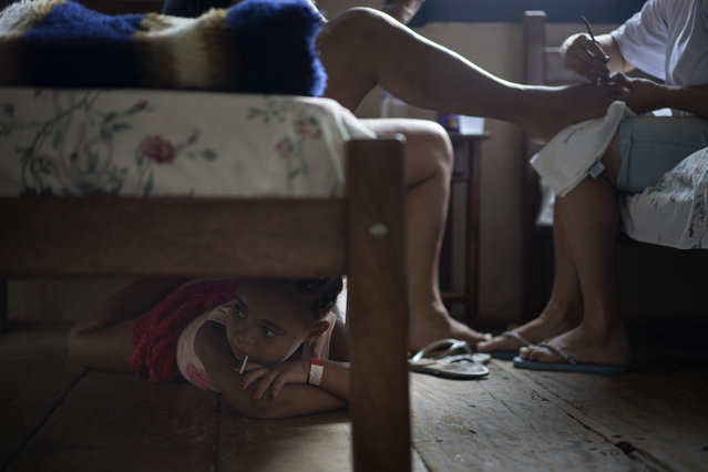 Five-year-old Nicole eats a lollipop under a bed while her mother gets a pedicure at a hotel housing people displaced from a dam failure, in Mariana, in the Brazilian state of Minas Gerais, Monday, November 9, 2015. Nicole's home was destroyed Thursday when two dams at an iron ore mine flooded Bento Rodrigues, a village in southeastern Brazil. Gov. Photo by Felipe Dana/AP Photo)