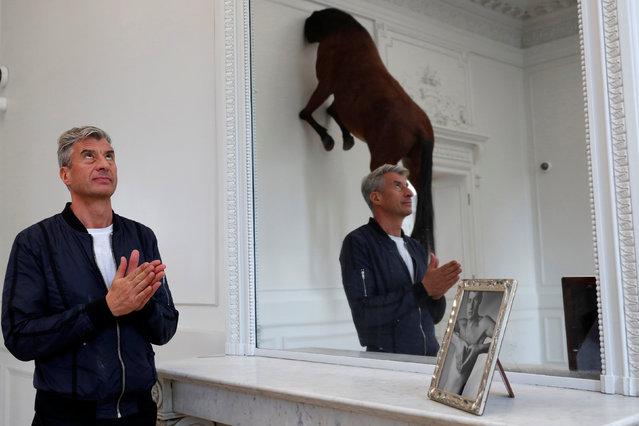 "Italian artist Maurizio Cattelan poses with his creation ""Untitled"" (2007), prior to the opening of the exhibition ""Not Afraid of Love"" at the Hotel de la Monnaie in Paris, France, October 17, 2016. (Photo by Philippe Wojazer/Reuters)"