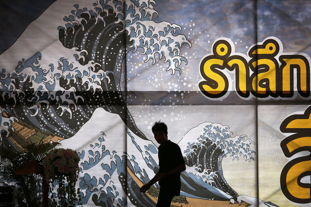 A man is silhouetted against a backdrop of an illustration of a tsunami as he prepares the stage for a memorial to mark the 10th anniversary when the Asian tsunami struck, Thursday, December 25, 2014 in Ban Nam Khem, Thailand. December 26 marks the 10th anniversary of one of the deadliest natural disasters in world history: a tsunami, triggered by a massive earthquake off the Indonesian coast, that left more than 230,000 people dead in 14 countries and caused about $10 billion in damage. (Photo by Wong Maye-E/AP Photo)