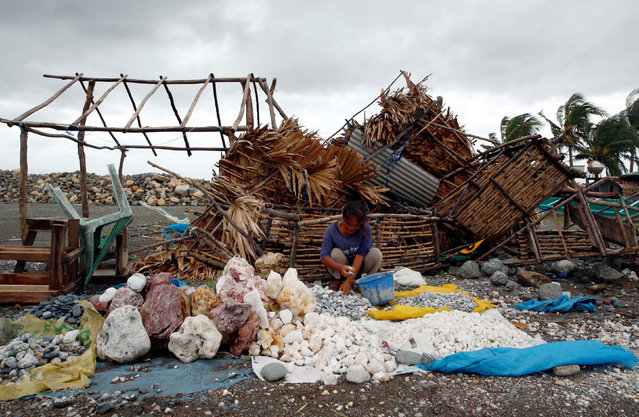 A woman sorts decorative rocks outside her shop toppled during Typhoon Haima, in Pasuiquin, Ilocos Norte in northern Philippines, October 20, 2016. (Photo by Erik De Castro/Reuters)