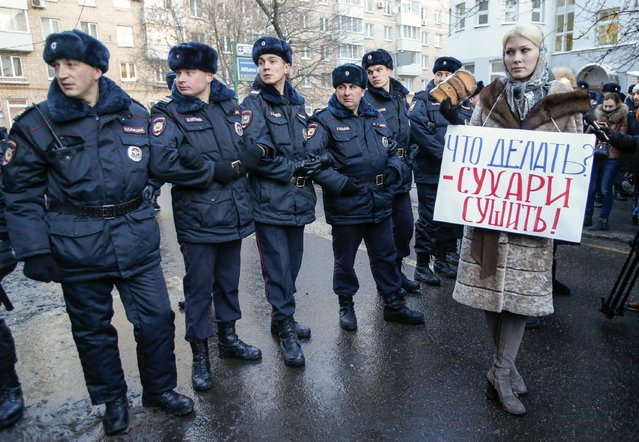 "A Pro-Kremlin opponent of opposition leader and anti-corruption blogger Alexei Navalny stands next to policemen blocking a street near a court building during his hearing in Moscow December 30, 2014. The sign reads ""What to do? – Dry hardtack!"". (Photo by Tatyana Makeyeva/Reuters)"