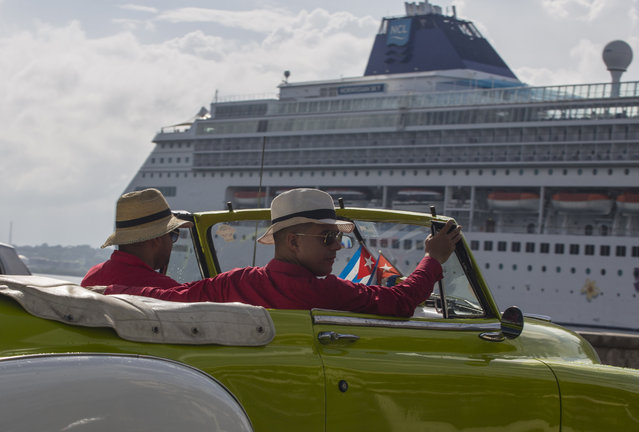 Local tour guides look for customers in their convertible car near a cruise ship docked in Havana, Cuba, Tuesday, October 3, 2017. Thousands of private Cuban businesses have invested heavily in private homes, cars and restaurants, hoping to cash in on an expected wave of American travelers to the island. Now that the U.S. State Department has issued a travel warning for the country, their investments are at risk. (Photo by Desmond Boylan/AP Photo)