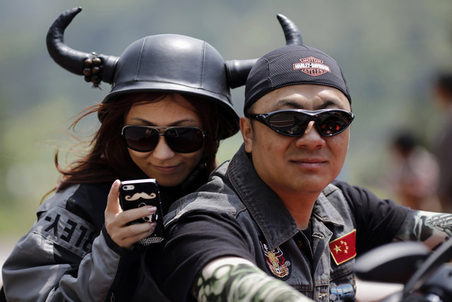 A couple rides a Harley Davidson motorcycle during the annual Harley Davidson National Rally in Qian Dao Lake, in Zhejiang Province, China, on May 11, 2013. Around 1,000 Harley Davidson enthusiasts from all over China met at the rally, as part of the company's 110-year anniversary. (Photo by Carlos Barria/Reuters)