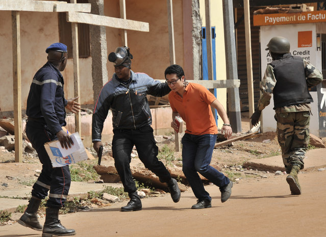 Malian security forces evacuate a man from an area surrounding the Radisson Blu hotel in Bamako on November 20, 2015. Gunmen went on a shooting rampage at the luxury hotel in Mali's capital Bamako, seizing 170 guests and staff in an ongoing hostage-taking that has left at least three people dead. (Photo by Habibou Kouyate/AFP Photo)