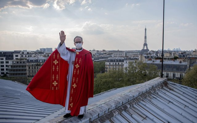 Father Bruno Lefevre Pontalis stands on the rooftop of Saint Francois Xavier church to bless the city of Paris during the national lockdown for Covid-19 at Easter, in Paris, France on April 12, 2020. (Photo by Nathan Laine/Bloomberg)
