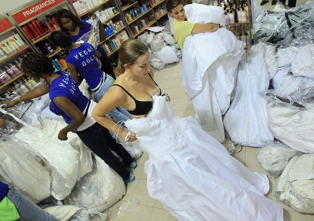 "Bride-to-be Amanda Joyce tries on a wedding gown during Filene's Basement's annual sale in Bethesda, Maryland. Hundreds of brides-to-be and their shopping teams line up early waiting to buy gowns at drastically low prices during the annual sale, dubbed the ""Running of the Brides"".  (Photo by Mark Wilson/Getty Images)"