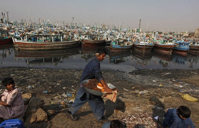 A man carries samosas to sell along Karachi's Fish Harbour December 31, 2014. (Photo by Akhtar Soomro/Reuters)