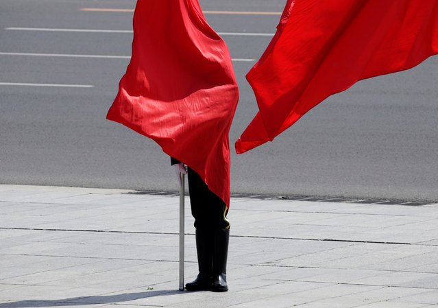 A soldier from the honour guards is covered by a red flag during a welcome ceremony for German Chancellor Angela Merkel outside the Great Hall of the People in Beijing, China May 24, 2018. (Photo by Jason Lee/Reuters)