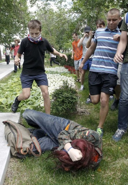 "Youths kick a gay rights activist during a protest against a proposed new law termed by the State Duma, the lower house of Parliament, as ""against advocating the rejection of traditional family values"" in central Moscow June 11, 2013. (Photo by Maxim Shemetov/Reuters)"
