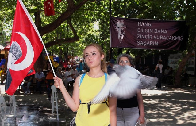Turks, some of them holding national flags with images of Turkey's founder Kemal Ataturk, stand in a silent protest in Kugulu Park in Ankara, Turkey, Wednesday, June 19, 2013. After weeks of sometimes-violent confrontation with police, Turkish protesters have found a new form of resistance: standing still and silent. (Photo by Burhan Ozbilic/AP Photo)