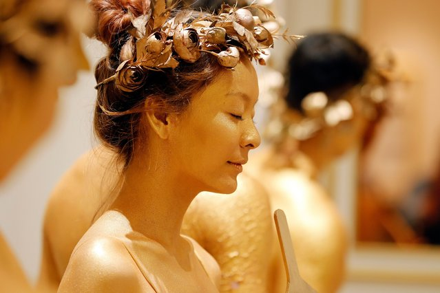 A model is seen backstage during a ceremony at the Dolce Hanoi Golden Lake hotel, a gold-covered accommodation built next to Giang Vo Lake and billed as Southeast Asia's most luxurious hotel in Hanoi, Vietnam 19 November 2020. The hotel is considered as the the first one in the world to have both the exterior and interior covered in gold. (Photo by Luong Thai Linh/EPA/EFE)