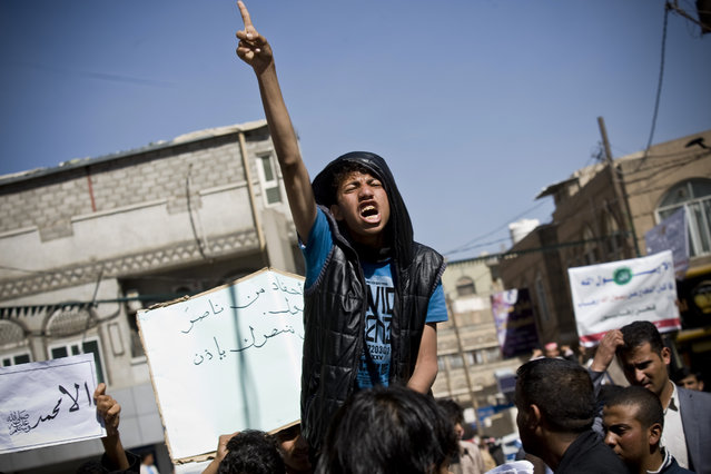 A Yemeni youth chants slogans during a protest against caricatures published in French magazine Charlie Hebdo in front of the French Embassy in Sanaa, Yemen, Saturday, January 17, 2015. (Photo by Hani Mohammed/AP Photo)