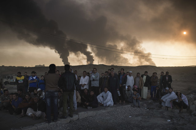 Men are held by Iraqi national security agents, to be interrogated at a checkpoint, as oil fields burn in Qayara, south of Mosul, Iraq, Saturday, November 5, 2016. Islamic State fighters launch counterattacks in the thin strip of territory Iraqi special forces have recaptured in eastern Mosul, highlighting the challenges ahead as the battle moves into more densely populated neighborhoods where coalition air power must be used more selectively. (Photo by Felipe Dana/AP Photo)