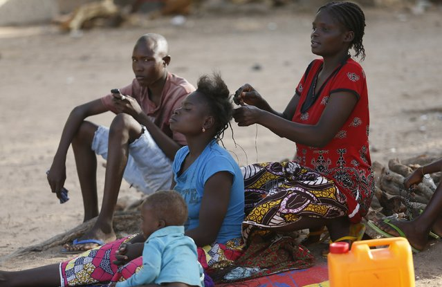 Women displaced as a result of Boko Haram attacks in the northeast region of Nigeria, spend the time fixing their hair at a camp for internally displaced people in Yola, Adamawa State January 14, 2015. (Photo by Afolabi Sotunde/Reuters)