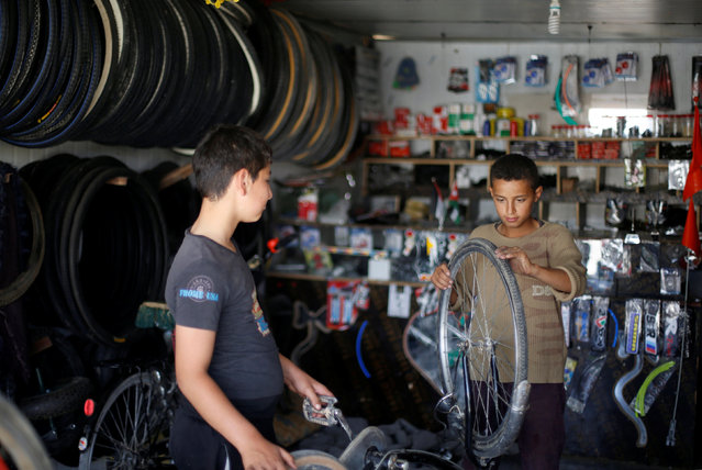 A Syrian refugee boy works at bicycle repair shop at the main market, in the Al-Zaatri refugee camp in the Jordanian city of Mafraq, Jordan, near the border with Syria September 17, 2016. (Photo by Muhammad Hamed/Reuters)