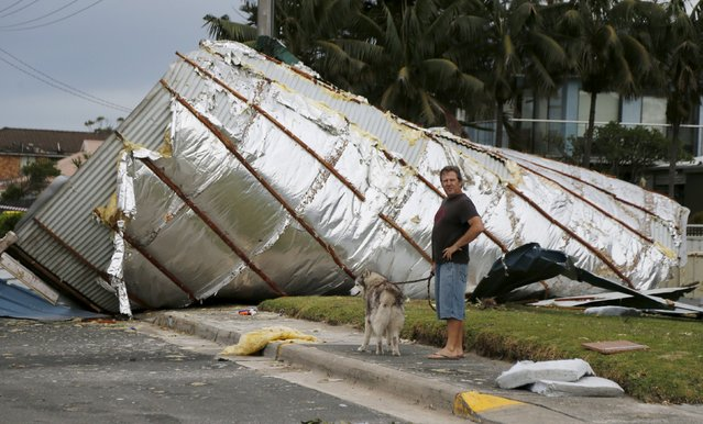 A resident from Sydney's southern suburb of Kurnell walks his dog past a house roof which had been blown down the street following a rare tornado, December 16, 2015. (Photo by Jason Reed/Reuters)