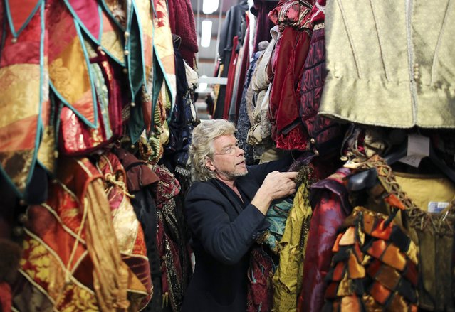 Costume designer Stefano Nicolao holds up a dress in his atelier in downtown Venice January 31, 2015. (Photo by Stefano Rellandini/Reuters)