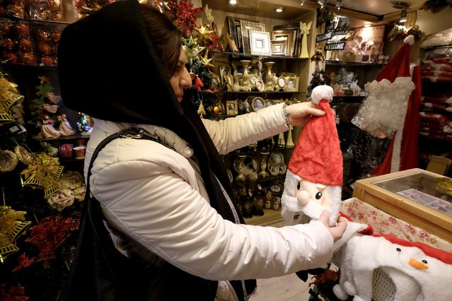 An Iranian Christian woman looks at a Santa Claus mask during her Christmas shopping at a shop in central Tehran December 23, 2015. (Photo by Raheb Homavandi/Reuters)