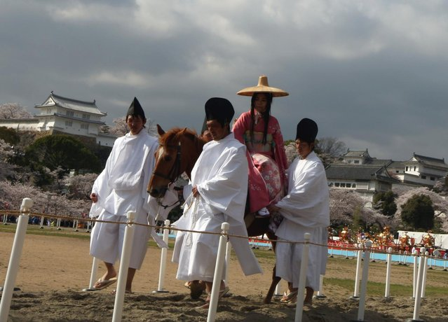 A woman wears tradional costume ride by horse for entertain the gods during the Mitsuyama Taisai Festival of Itate Hyozu Shrine at front of the Himeji castle on April 3, 2013 in Himeji, Japan. (Photo by Buddhika Weerasinghe/Getty Images)