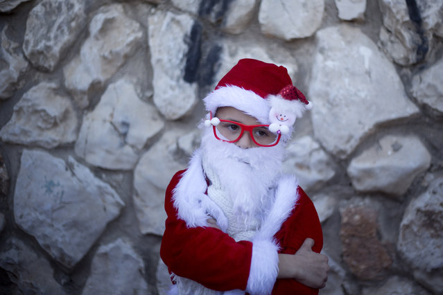An Israeli Arab Christian boy dressed up as Santa Claus waits for the start of the annual Christmas parade in in the northern Israeli city of Nazareth, Israel, Thursday, December 24, 2015. (Photo by Ariel Schalit/AP Photo)