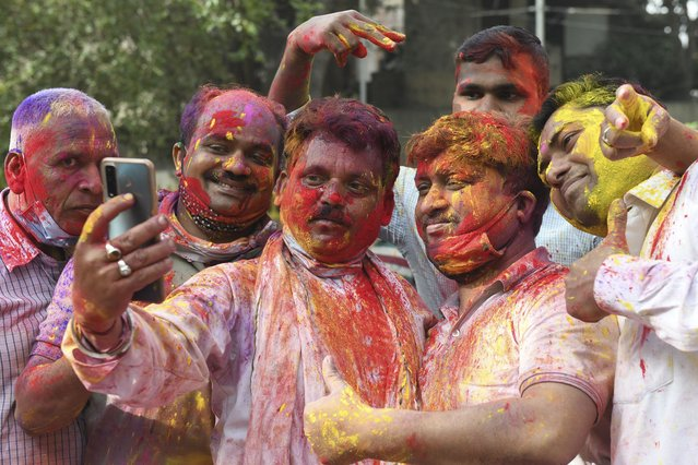 Revellers smeared in colour powder take selfie pictures as they celebrate Holi, the spring festival of colours, in Amritsar on March 29, 2021. (Photo by Narinder Nanu/AFP Photo)