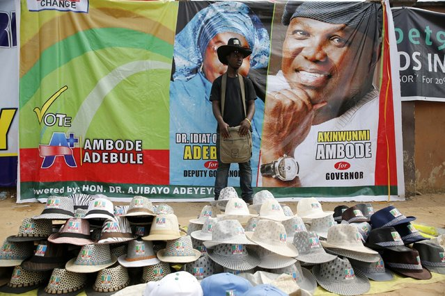 Michael Chijoke Ano, 21, who is a student and an ethnic Igbo man from Nigeria's eastern region, waits for customers during a campaign for the governorship candidate Akinwunmi Ambode, of the All Progressives Congress (APC), in Oworonshoki district in Lagos January 19, 2015. Ano sells party souvenirs to support his education and he hopes that the election is devoid of violence so that his education plans are not affected. (Photo by Akintunde Akinleye/Reuters)