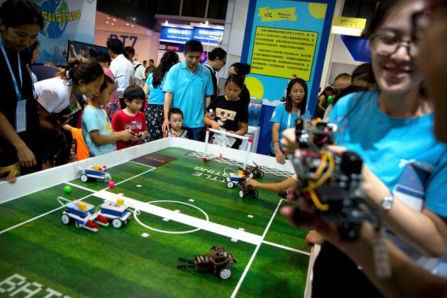Children play with small robots at a display from Chinese online robot education platform Roborobo at the World Robot Conference in Beijing, China, Wednesday, August 15, 2018. (Photo by Mark Schiefelbein/AP Photo)