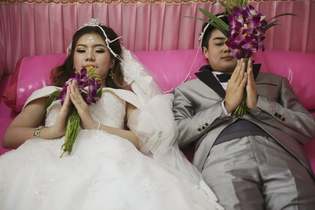 Pichaya Tantip (R) and her partner Phatrnaya Kamploy, a same s*x couple, lie inside a pink coffin during their wedding ceremony at Wat Takien temple in Nonthaburi province, on the outskirts of Bangkok February 14, 2015. (Photo by Damir Sagolj/Reuters)