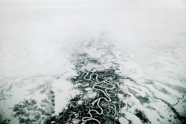 "2013. Seen from an airplane, a waterway snakes its way through the frozen tundra. At 400 kilometers above the Arctic Circle, Norilsk, Russia, is not accessible by road or rail, only by air and waterways when they're not frozen. The rest of the world is referred to as ""the continent"". (Photo by Elena Chernyshova)"