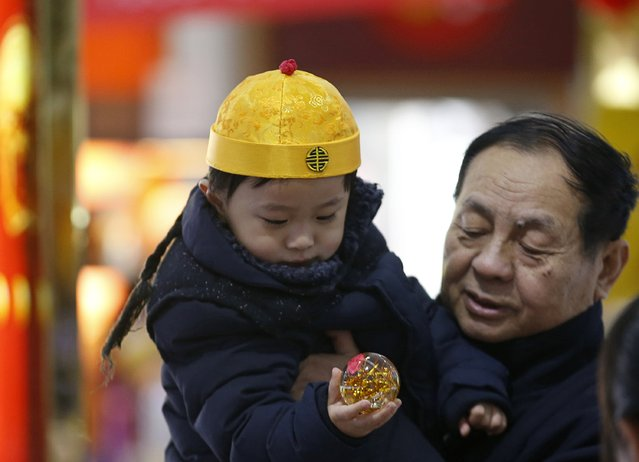 A boy wearing a traditional hat chooses a toy at a shopping mall in Beijing February 17, 2015. (Photo by Kim Kyung-Hoon/Reuters)