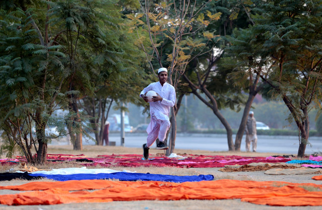 A seminary student retrieves a volleyball from between tablecloths drying in the grass in Islamabad, Pakistan December 3,  2016. (Photo by Caren Firouz/Reuters)