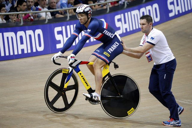 Francois Pervis of France is assisted by his coach Franck Durivaux (R) before starting in the men's keirin track cycling event at the UCI Track Cycling World Cup in Saint-Quentin-en-Yvelines, near Paris, February 19, 2015. Pervis won the event. (Photo by Charles Platiau/Reuters)