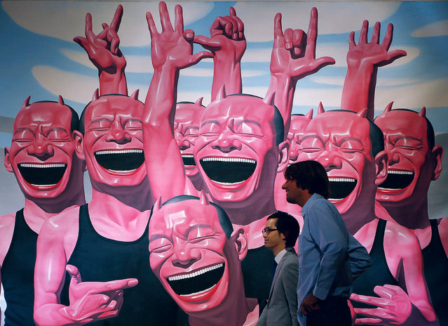 """Two men walk past a painting by Chinese artist Yue Minjun titled """"Between Men and Animal""""  during a press preview for a Sotheby's auction in Hong Kong, Wednesday, October 2, 2013. The work is estimated at US$644,650 to 1,031,440 and will be auctioned as part of the autumn sale from October 4–8. (Photo by Vincent Yu/AP Photo)"""