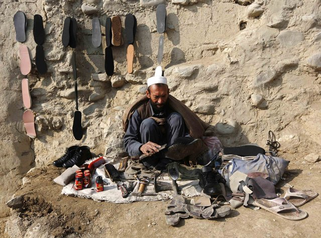 A cobbler sits at a roadside as he brushes a customer's shoes in Kabul, January 26, 2015. (Photo by Omar Sobhani/Reuters)