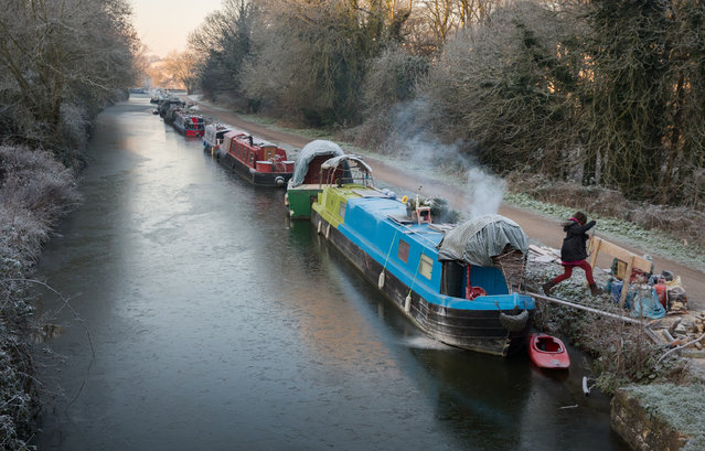 A woman leaps from a narrowboat moored on the frozen Kennet and Avon canal at Bathampton on January 20, 2016 in Bath, England. Many parts of the UK experienced subzero temperatures last night with the Met Office saying that the lowest  temperatures recorded in England were –8C in Berkshire. (Photo by Matt Cardy/Getty Images)