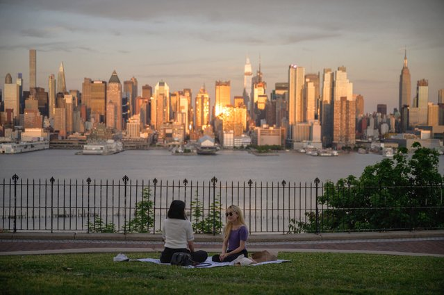 A general view shows people sitting before the Manhattan city skyline at a park in New Jersey, on May 27, 2021. (Photo by Ed Jones/AFP Photo)