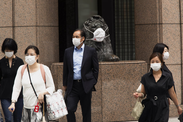 People wearing face masks walk across a traffic intersection, passing by a statue of a lion with a face mask displayed at a department store in the famed Ginza shopping neighborhood in Tokyo on Friday, May 21, 2021. Japan has approved the use of two new vaccines – Moderna and AstraZeneca – hours ahead of an expansion of a state of coronavirus emergency that will cover roughly 40% of the population. It's the latest effort to contain a worrying surge in infections nine weeks ahead of the opening of the Tokyo Olympics. (Photo by Hiro Komae/AP Photo)
