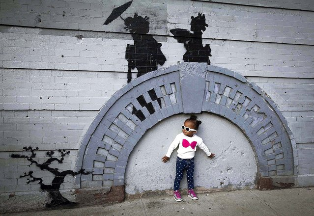 A child poses for a photo under the art piece by Banksy on October 17, 2013 before the metal gate was installed. (Photo by Carlo Allegri/Reuters)