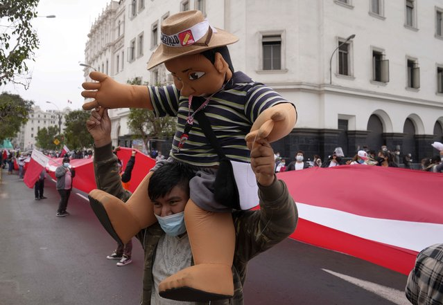 A supporter of presidential candidate Pedro Castillo carries a puppet in Castillo's likeness during a march in Lima, Peru, Wednesday, June 9, 2021. Peruvians are still waiting to learn who will become their president next month as votes from Sunday's runoff election continued to be counted and the tiny difference between the two polarizing populist candidates narrowed. (Photo by Martin Mejia/AP Photo)