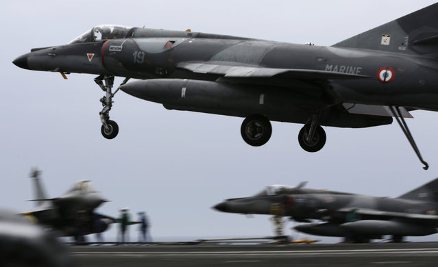 In this Tuesday, March 17, 2015 photo, a French military plane lands on the flight deck of the French Navy aircraft carrier Charles de Gaulle, in the Persian Gulf. (Photo by Hasan Jamali/AP Photo)