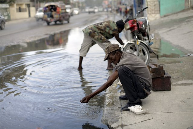 A man washes his hands in a puddle in Port-au-Prince, Haiti, January 27, 2016. Zika outbreaks have been reported in Haiti. The virus is spread by the Aedes aegypti mosquito, which is notoriously adaptive. The insect thrives in puddles, nooks and crannies common in tropical cities peppered with chaotic and unplanned neighbourhoods, where rainwater, open sewers and litter offer ample habitat. (Photo by Andres Martinez Casares/Reuters)