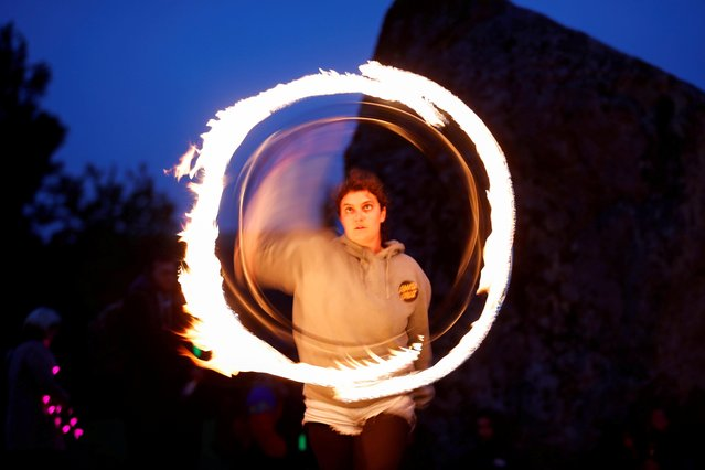 A person performs with fire during the celebration of the Summer Solstice, despite official events being cancelled amid the spread of the coronavirus disease (COVID-19), in Avebury, Britain, June 21, 2021. Picture taken with long exposure. (Photo by Andrew Boyers/Reuters)