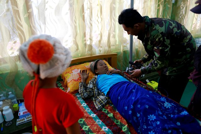 A military doctor attends to a woman who fled from violence in Laukkai, Kokang region, at a temporary refugee camp set up in a monastery in Lashio February 19, 2015. (Photo by Soe Zeya Tun/Reuters)