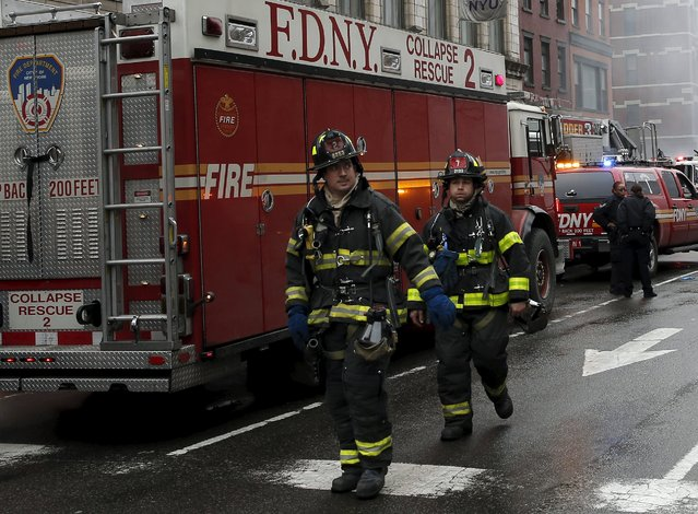 New York City Fire Department firefighters walk away from the site where a residential apartment building collapsed and was engulfed in flames in New York City's East Village neighborhood March 26, 2015. (Photo by Mike Segar/Reuters)