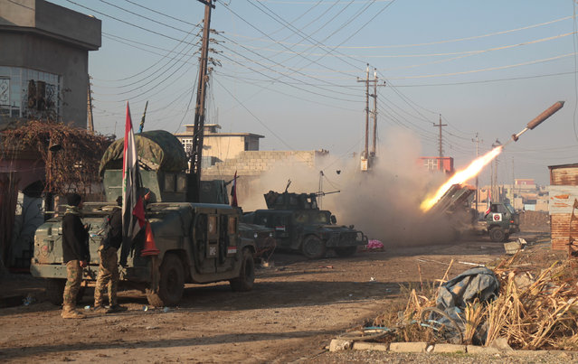Iraqi forces launch a rocket in Mosul's eastern Al-Intisar neighbourhood on December 30, 2016, during an ongoing military operation against Islamic State (IS) group jihadists. Iraqi forces advanced on December 29 after declaring a new phase in their offensive on eastern Mosul, stepping up efforts to reclaim the Islamic State group's last major stronghold in the country. (Photo by Ahmad Al-Rubaye/AFP Photo)