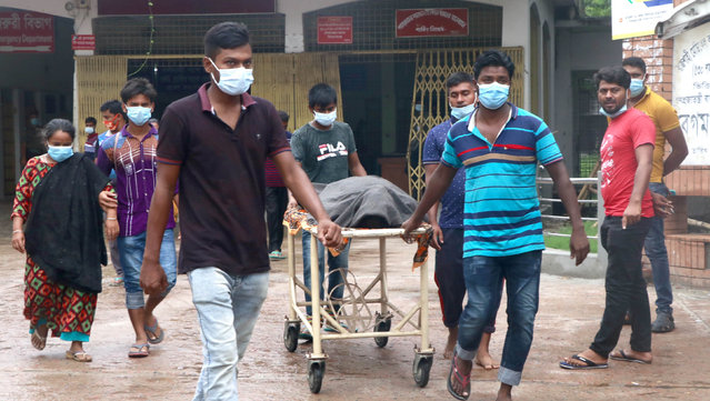 People leave a hospital with the body of a relative at the Medical College Hospital in Rajshahi, 254 kilometers (158 miles) north of the capital, Dhaka, Bangladesh, June 15, 2021. (Photo by Kabir Tuhin/AP Photo)