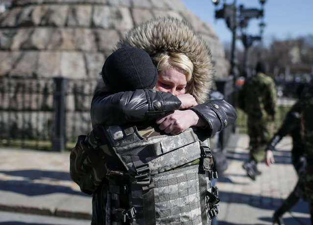 A relative of a member of the Organization of Ukrainian Nationalists (OUN) reacts before volunteers depart to the frontlines in eastern Ukraine, in central Kiev, March 17, 2015. (Photo by Gleb Garanich/Reuters)